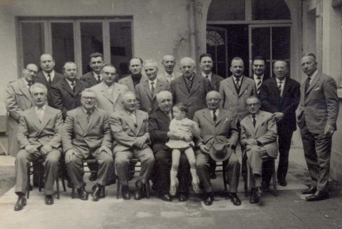 L'ACCADEMIA NEL 1960 Una foto storica del 1960 delle origini dell'Accademia dei Maestri Artigiani. IN PIEDI: il cementista EDMONDO CARLINI (il 6° da sinistra con la camicia nera), ORESTE CAPPELLARI per decenni coordinatore dell'Accademia (il 5° da destra), il fabbro ALFONSINO NAVARRA (il 4° da destra), il rilegatore GABRIELE CAPPELLARI (il 3° da destra), MARIO RIZZARDI (il 2° da destra), il marmista GHEDINI (il 1° da destra). SEDUTI: il sarto DANTE BARATELLA (il 1° da destra), il fabbro EFREM NAVARRA (il 2° da destra con il cappello in mano), il rilegatore PILADE CAPPELLARI con in braccio in nipote Lorenzo.